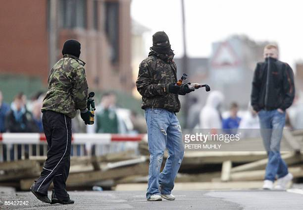 Masked youths prepare to throw molotov cocktails as they block the railway line near the house of former Irish Republican Army man Colin Duffy in...