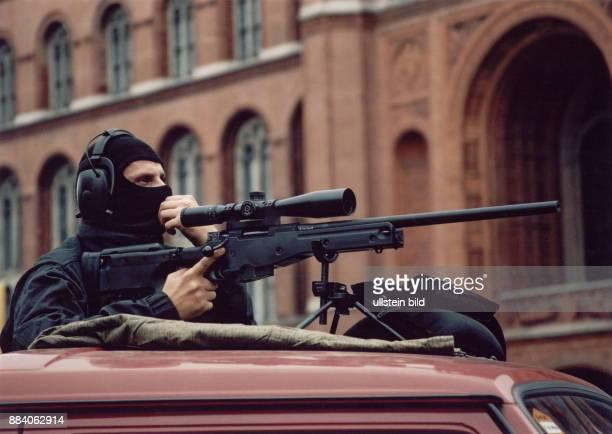 maskierter Scharfschütze der bei einem Einsatz sein Gewehr auf einem Autodach positioniert hat 2002