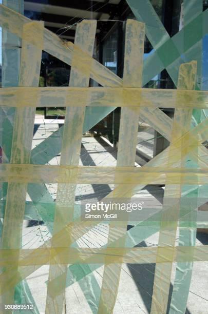 Masking tape holding together shattered glass in a vandalised bus shelter