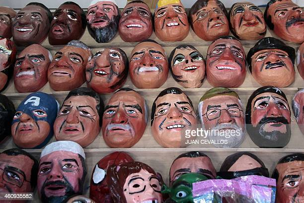 Masks are sold at a stand in the street during Ecuador's traditional New Year custom of burning dummies representing prominent politicians sport...