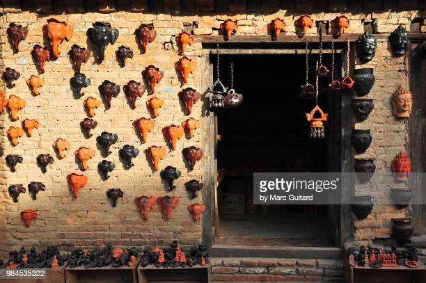 masks for sale on the wall of a small shop, bhaktapur, kathmandu valley, nepal - kathmandu stock pictures, royalty-free photos & images