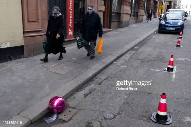 Mask-wearing Londoners walk past a split pink plastic sphere which has come to rest in the gutter on a side street in central London, during the...