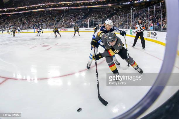 Mason Appleton of the Winnipeg Jets battles Tomas Nosek of the Vegas Golden Knights as they chase the loose puck along the corner boards during first...