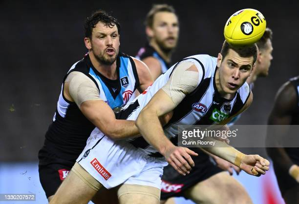 Mason Cox of the Magpies handballs whilst being tackled by Travis Boak of the Power during the round 19 AFL match between Port Adelaide Power and...