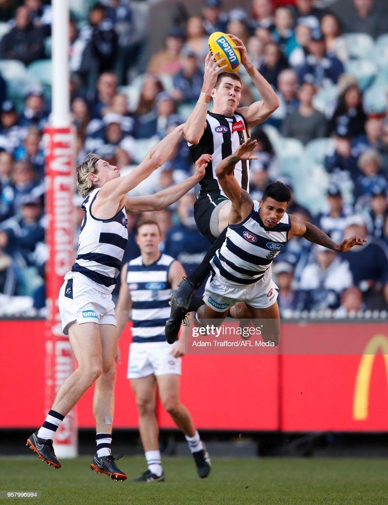 Mason Cox of the Magpies marks the ball over Tim Kelly (right) and Mark Blicavs of the Cats during the 2018 AFL round eight match between the Collingwood Magpies and the Geelong Cats at the Melbourne Cricket Ground on May 13, 2018 in Melbourne, Australia.