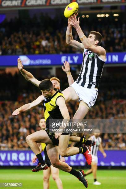 Mason Cox of the Magpies marks the ball over Trent Cotchin of the Tigers during the AFL Preliminary Final match between the Richmond Tigers and the...