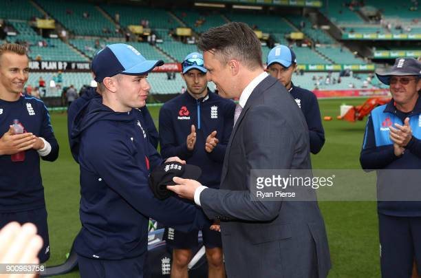 Mason Crane of England receives his test cap from former England cricketer Graeme Swann during day one of the Fifth Test match in the 2017/18 Ashes...