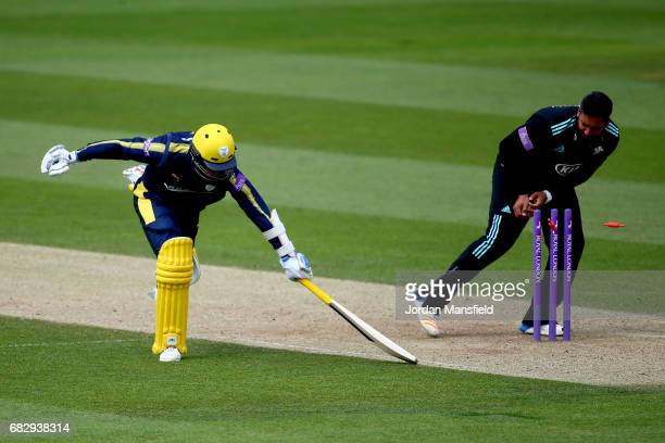 Mason Crane of Hampshire lunges to make his ground as Ravi Rampaul of Surrey takes the bails off during the Royal London OneDay Cup match between...