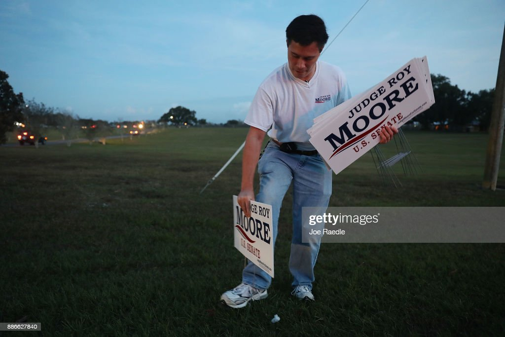 Mason Green puts out campaign signs for Republican Senatorial candidate Roy Moore before a rally at Oak Hollow Farm on December 5, 2017 in Fairhope, Alabama. Mr. Moore is facing off against Democrat Doug Jones in next week's special election for the U.S. Senate.