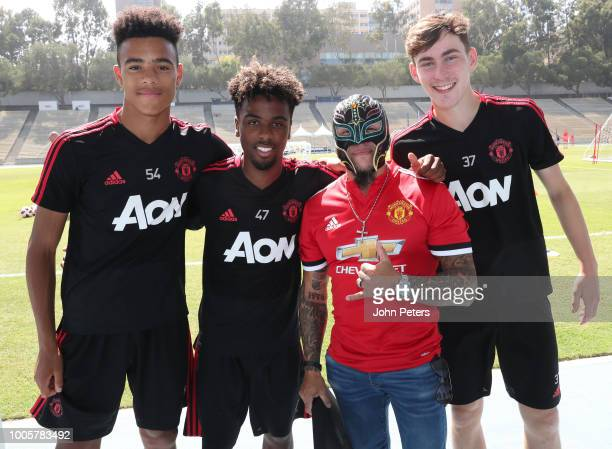 Mason Greenwood Angel Gomes and James Garner of Manchester United pose with wrestler Rey Mysterio during a Manchester United preseason training...