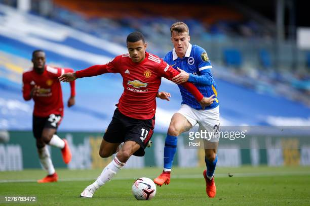 Mason Greenwood of Manchester United battles for possession with Solly March of Brighton and Hove Albion during the Premier League match between...