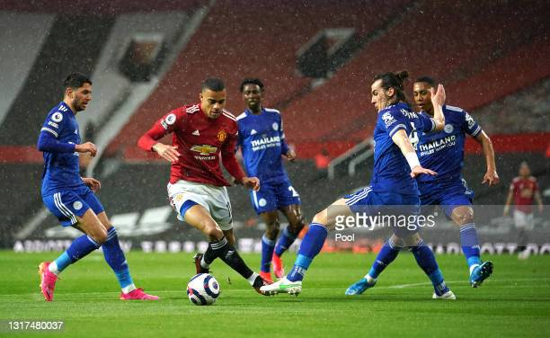 Mason Greenwood of Manchester United gets away from Ayoze Perez and Caglar Soyuncu of Leicester City before scoring their side's first goal during...