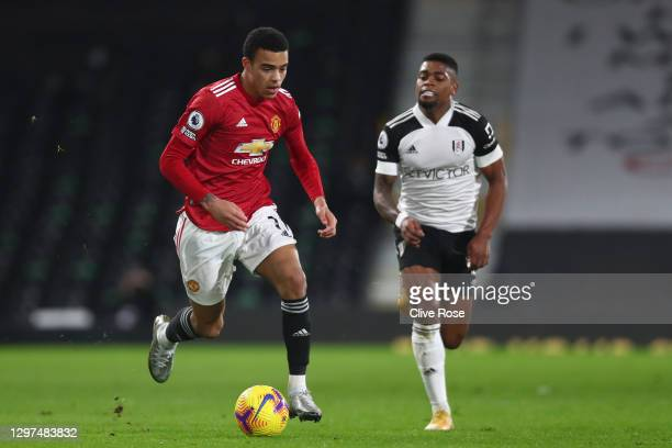 Mason Greenwood of Manchester United runs with the ball under pressure from Ivan Cavaleiro of Fulham during the Premier League match between Fulham...
