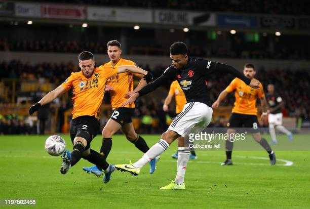 Mason Greenwood of Manchester United shoots under pressure from Matt Doherty of Wolverhampton Wanderers during the FA Cup Third Round match between...