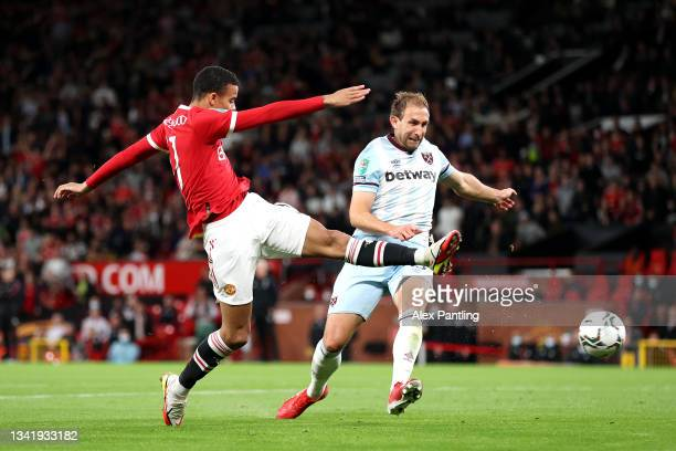 Mason Greenwood of Manchester United shoots whilst under pressure from Craig Dawson of West Ham United during the Carabao Cup Third Round match...