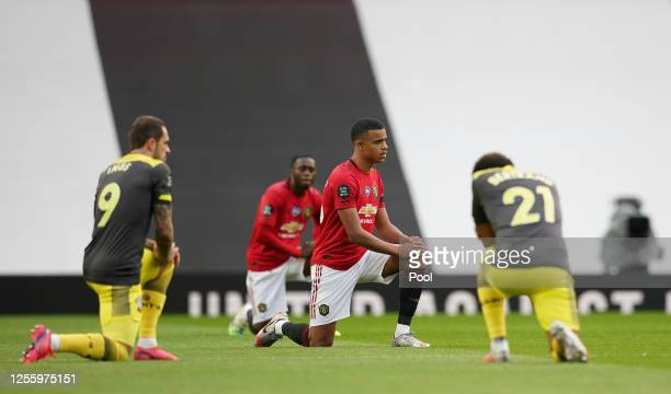 Mason Greenwood of Manchester United takes a knee in support of the Black Lives Matter movement prior to the Premier League match between Manchester...
