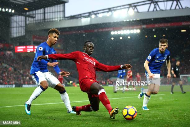 Mason Holgate and Jonjoe Kenny of Everton try to challenge Sadio Mane of Liverpool battle for possesion during the Premier League match between...