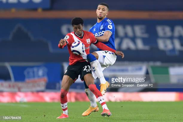Mason Holgate of Everton and Nathan Tella challenge for the ball during the Premier League match between Everton and Southampton at Goodison Park on...