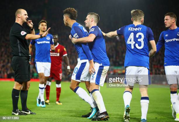 Mason Holgate of Everton is restrained by Morgan Schneiderlin of Everton after a clash with Roberto Firmino of Liverpool as referee Robert Madley...