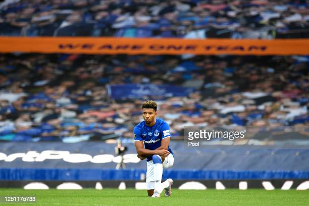 Mason Holgate of Everton takes a knee in support of the Black Lives Matter movement during the Premier League match between Everton FC and Liverpool...