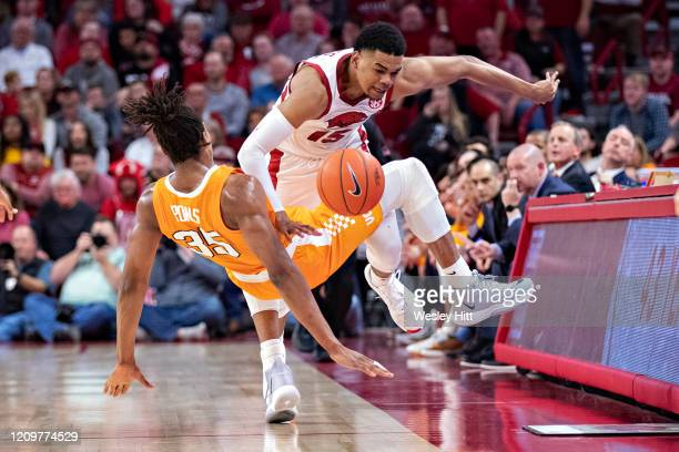 Mason Jones of the Arkansas Razorbacks draws a foul against Yves Pons of the Tennessee Volunteers at Bud Walton Arena on February 26, 2020 in...