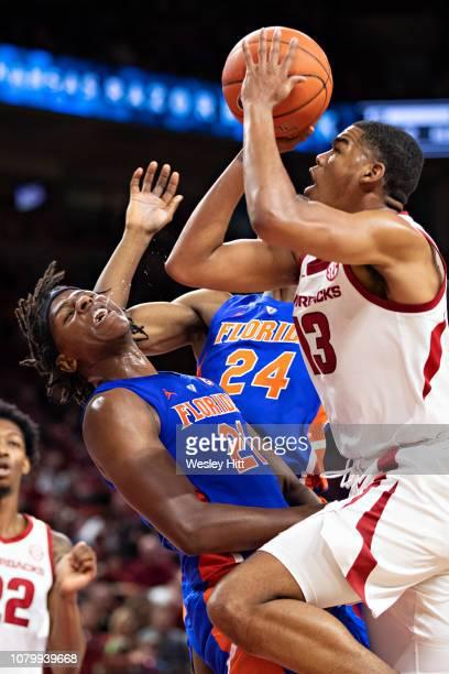 Mason Jones of the Arkansas Razorbacks drives to the basket and is fouled by Dontay Bassett of the Florida Gators at Bud Walton Arena on January 9,...