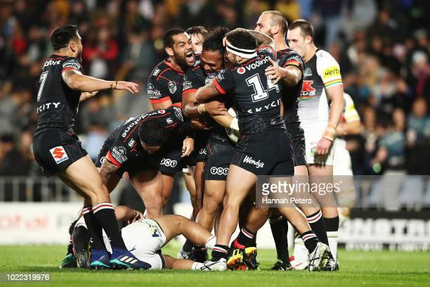 Mason Lino of the Warriors celebrates with the team after scoring a try during the round 24 NRL match between the New Zealand Warriors and the...