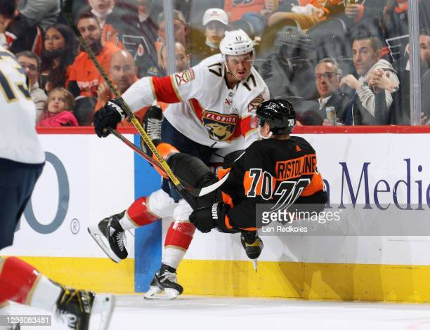 Mason Marchment of the Florida Panthers checks Rasmus Ristolainen of the Philadelphia Flyers along the boards at the Wells Fargo Center on October...