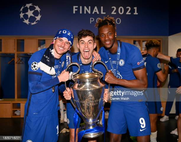 Mason Mount, Kai Havertz and Tammy Abraham of Chelsea celebrate in the dressing room with the Champions League Trophy following their team's victory...