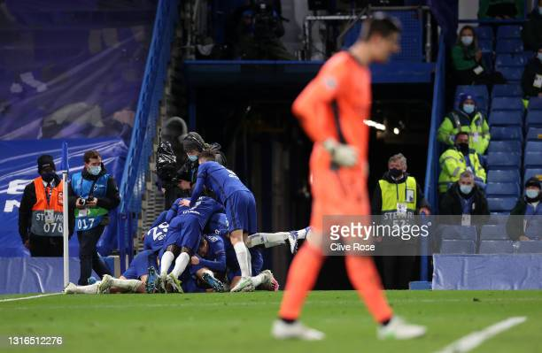 Mason Mount of Chelsea celebrates with teammates after scoring their team's second goal as Thibaut Courtois of Real Madrid looks dejected during the...