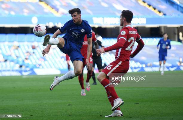 Mason Mount of Chelsea controls the ball under pressure from Andy Robertson of Liverpool during the Premier League match between Chelsea and...