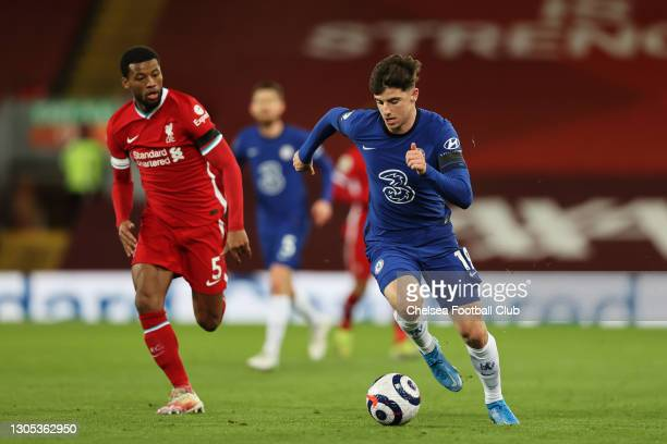 Mason Mount of Chelsea runs with the ball as he is chased by Georginio Wijnaldum of Liverpool during the Premier League match between Liverpool and...