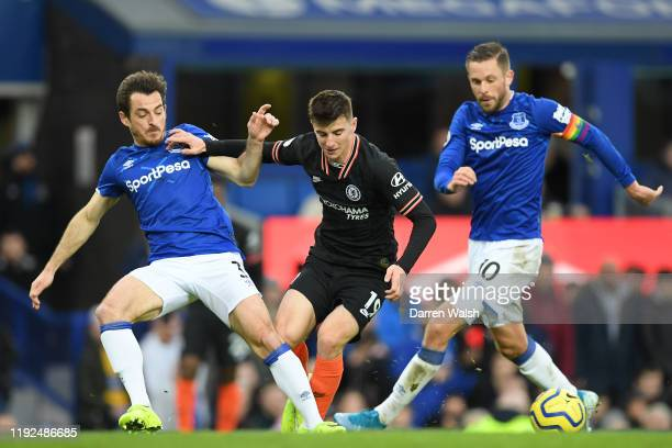 Mason Mount of Chelsea runs with the ball as he is put under pressure by Leighton Baines and Gylfi Sigurdsson of Everton during the Premier League...