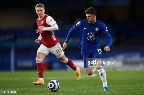 Mason Mount of Chelsea runs with the ball whilst under pressure from Martin Odegaard of Arsenal during the Premier League match between Chelsea and...