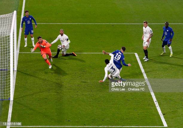 Mason Mount of Chelsea scores his team's second goal under pressure from Eder Militao of Real Madrid past Thibaut Courtois of Real Madrid during the...