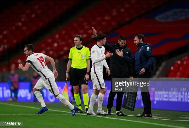 Mason Mount of England speaks with Gareth Southgate, Manager of England as he leaves the pitch following substitution for team mate Harry Winks...