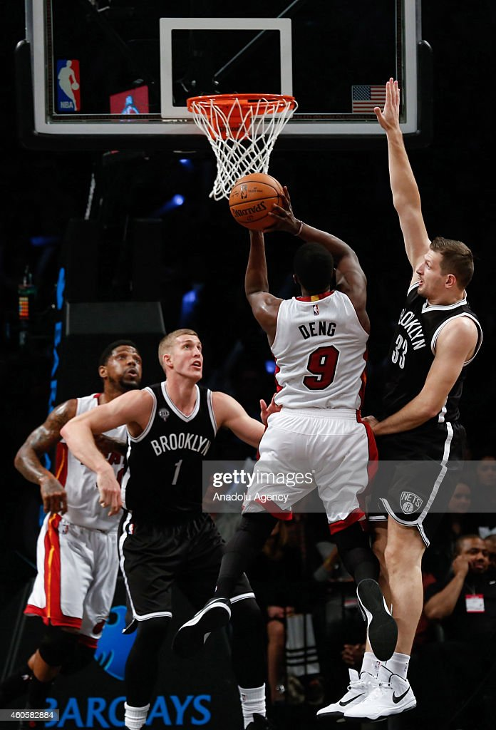 Mason Plumlee #1 and Mirza Teletovic #33 of the Brooklyn Nets in action against Luol Deng #9 of Miami Heat during NBA basketball game between Brooklyn Nets and Miami Heat at the Barclays Center in the Brooklyn Borough of New York City, on December 16, 2014.