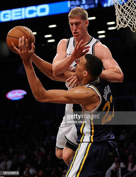 Mason Plumlee of the Brooklyn Nets jumps to block Rudy Gobert of the Utah Jazz during the second half at Barclays Center on November 5 2013 in the...