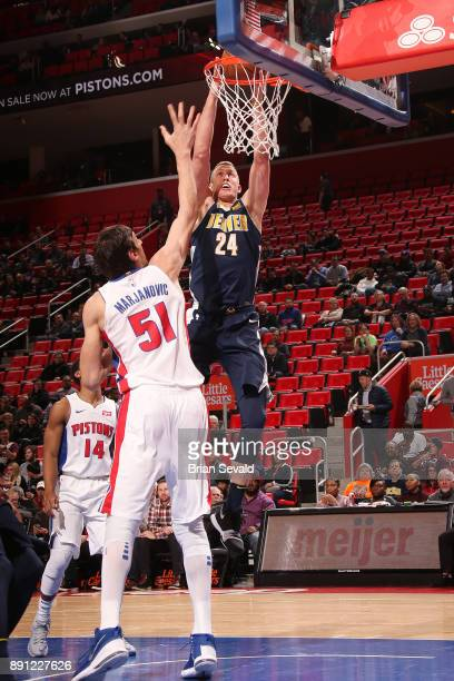 Mason Plumlee of the Denver Nuggets drives to the basket against the Detroit Pistons on December 12 2017 at Little Caesars Arena in Detroit Michigan...