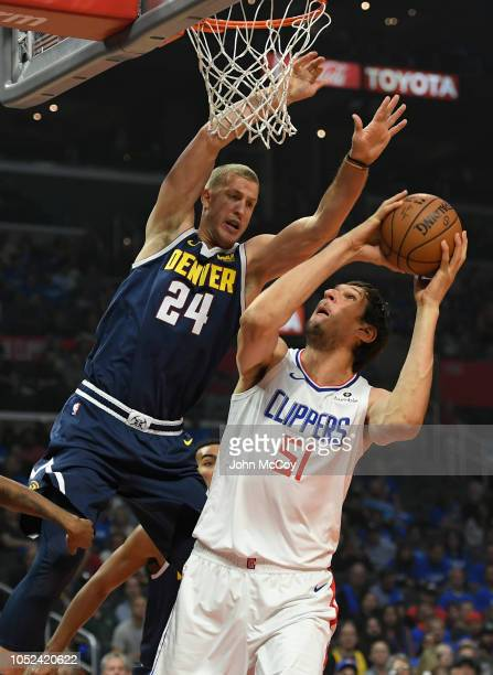 Mason Plumlee of the Denver Nuggets fouls Boban Marjanovic of the LA Clippers in the first half during the season opening game at Staples Center on...