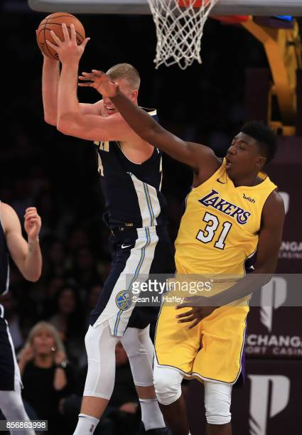 Mason Plumlee of the Denver Nuggets rebounds over Thomas Bryant of the Los Angeles Lakers during the first half of a preseason game at Staples Center...