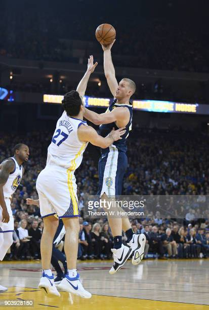 Mason Plumlee of the Denver Nuggets shoots over Zaza Pachulia of the Golden State Warriors during an NBA Basketballl game at ORACLE Arena on January...