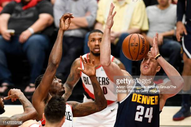 Mason Plumlee of the Denver Nuggets wears a ball to the face after it was hit by AlFarouq Aminu of the Portland Trail Blazers during the third...