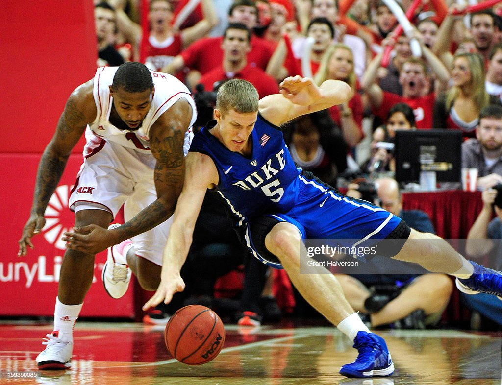Mason Plumlee #5 of the Duke Blue Devils battles for a loose ball with Richard Howell #1 of the North Carolina State Wolfpack during play at PNC Arena on January 12, 2013 in Raleigh, North Carolina.