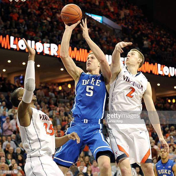 Mason Plumlee of the Duke Blue Devils goes to the hoop against Akil Mitchell and Paul Jesperson of the Virginia Cavaliers at John Paul Jones Arena on...