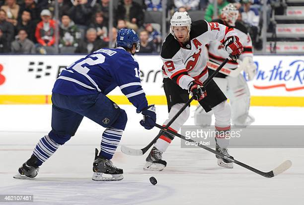 Mason Raymond of the Toronto Maple Leafs defends as Travis Zajac of the New Jersey Devils passes the puck during NHL game action January 12 2014 at...