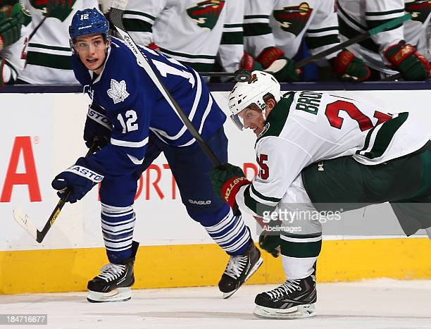 Mason Raymond of the Toronto Maple Leafs flips the puck past Jonas Brodin of the Minnesota Wild for an open net goal during NHL action at the Air...