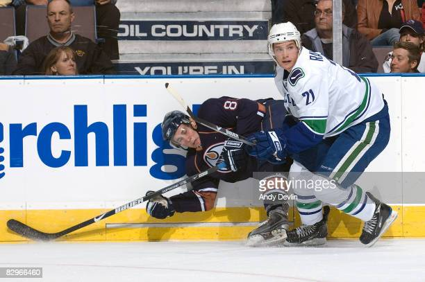 Mason Raymond of the Vancouver Canucks knocks Sam Gagner of the Edmonton Oilers to the ice during a preseason game on September 22 2008 at Rexall...