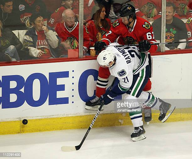 Mason Raymond of the Vancouver Canucks pins Michael Frolik of the Chicago Blackhawks to the boards as he chases down the puck in Game Three of the...