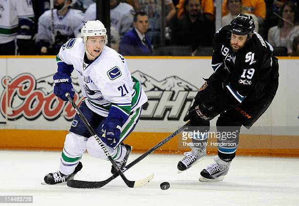 Mason Raymond of the Vancouver Canucks plays the puck in the neutral zone under pressure from Joe Thornton of the San Jose Sharks in Game Three of...